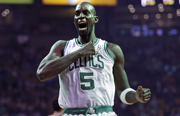 Boston Celtics forward Kevin Garnett pounds his chest as he heads to the floor to face the Milwaukee Bucks in the team's home opener before the tip-off of an NBA basketball game in Boston, Friday, Nov. 2, 2012. (AP Photo/Charles Krupa)