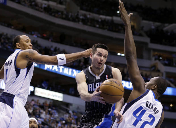 Dallas Mavericks' Shawn Marion, left, and Elton Brand (42) defend as Orlando Magic's J.J. Redick makes a pass beneath the basket during the first half of an NBA basketball game Wednesday, Feb. 20, 2013, in Dallas. (AP Photo/Tony Gutierrez)