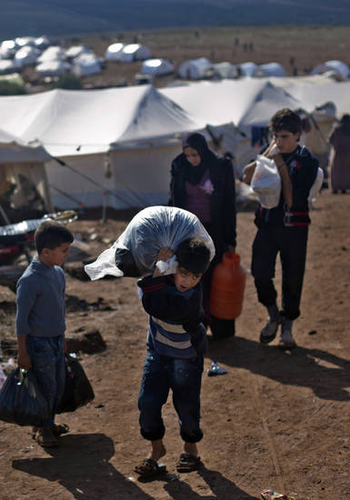 A Syrian boy who fled with his family from the violence in their village, carries a plastic bag as he walks to his tent at a displaced camp, in the Syrian village of Atma, near the Turkish border with Syria. Saturday, Nov. 10, 2012. (AP Photo/ Khalil Hamra)