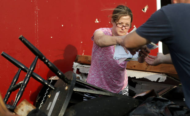 Nancy Townsend hands her husband, Jason Townsend, items as they sort through belongings after their home was destroyed Sunday by a tornado in Carney, OK. The Townsend's left their home to avoid the tornado. Photo by Bryan Terry, The Oklahoman <strong>Bryan Terry</strong>