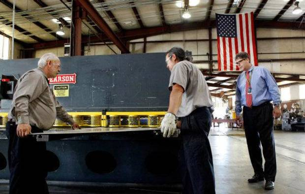 Stephen Benefield, right,  managing officer at Choctaw Defense, a growing company owned by the Choctaw Nation that has lucrative contracts with the Department of Defense, visits workers in the company's machine shop. He watches John Adams, left, and Fred Barnett lift a large section of sheet metal onto a  machine that  makes precise cuts.   The company  manufactures shipping containers, trailers and other heavy equipment used by the military. Their plant is located in the Choctaw Business Park on the south side of McAlester.   Photos taken Thursday, June 23, 2011   Photo by Jim Beckel, The Oklahoman ORG XMIT: KOD