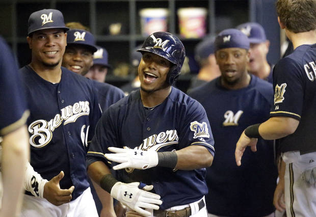 Milwaukee Brewers' Jean Segura, center, celebrates in the dugout after hitting a home run during the fifth inning of a baseball game against the Atlanta Braves, Friday, June 21, 2013, in Milwaukee. (AP Photo/Morry Gash)