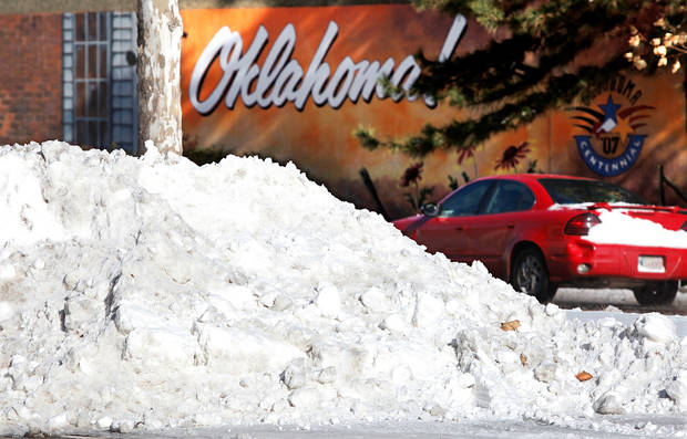 A car drives past a deep pile of snow after crews worked all day to clear downtown streets. This is at intersection of E.K. Gaylord and Sheridan. Many spent Christmas Day, Dec. 25, 2009,  digging out from record snow storm that dumped 14 inches of snow in the Oklahoma City area. The wording in background is part of a blocks-long mural on the railroad overpass.   Photo by Jim Beckel, The Oklahoman