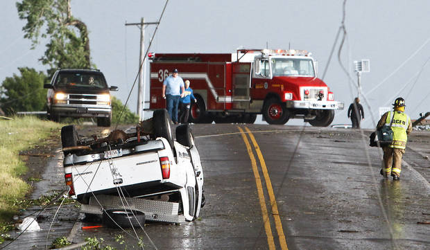 Power lines cross the road where a truck flipped over as a tornado damaged the area around Interstate 240 and Choctaw Road on Monday in Oklahoma City. Photo by Chris Landsberger, The Oklahoman