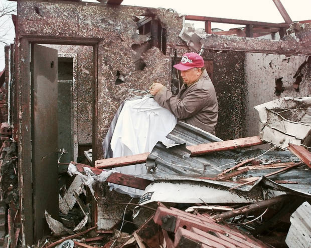 MAY 3, 1999 TORNADO: Tornado victims, damage: Area of NW 27TH AND I-35 IN MOORE OKLA.  Oklahoman reporter Nolan Clay removing clothing from a closet at his house on the corner of Bellaire and Cedar Lane in Moore.  (Nolans Clay's housing addition Highland Park) Just south of the First Baptist Church.
