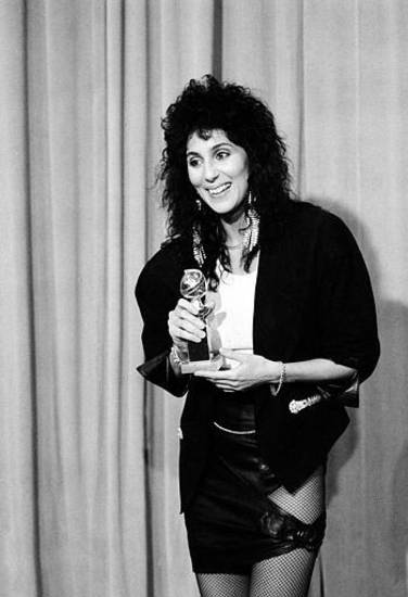 "Actress and singer Cher smiles with her award at the annual Golden Globe Awards presentation in Hollywood, Ca., Jan. 29, 1984.  Cher won for best supporting actress in the movie ""Silkwood.""  (AP Photo/Lennox McLendon)"