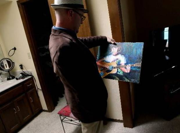 After work,  Jim pauses in his bedroom to look at a painting that a family friend made of  Jim's son Ford on Wednesday, April 8, 2009. Photo by John Clanton.