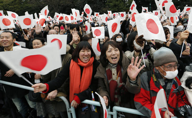 Well-wishers wave Japanese flags as Japan's Emperor Akihito makes a public appearance on a balcony of the Imperial Palace in Tokyo Sunday, Dec. 23, 2012. Emperor Akihito along with imperial family members received greetings from well-wishers to celebrate his 79th birthday.  (AP Photo/Shizuo Kambayashi)