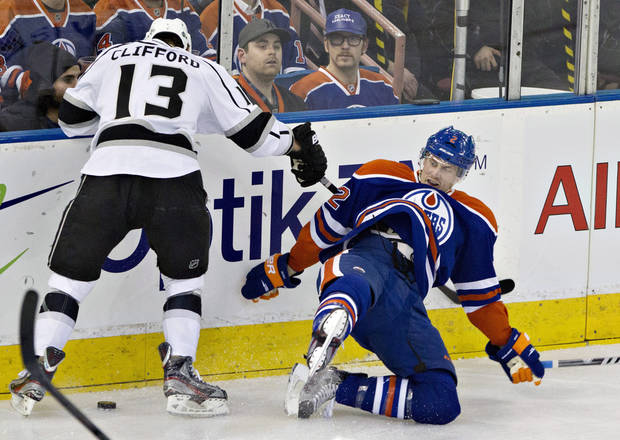 Los Angeles Kings' Kyle Clifford, left, checks Edmonton Oilers' Jeff Petry during second period NHL hockey action in Edmonton, Alberta, on Tuesday Feb. 19, 2013. (AP Photo/THE CANADIAN PRESS,Jason Franson)