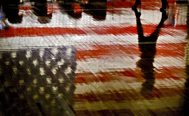 The American Flag reflects on the gym floor as a students walks by during the Yukon High School's Veteran's Day Celebration on Monday Nov. 712 2012, in Yukon, Oklahoma. Photo by Chris Landsberger, The Oklahoman