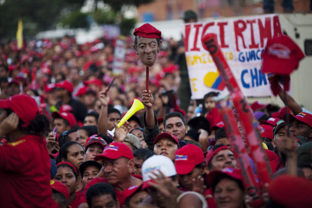Supporters of Venezuela's President Hugo Chavez, one holding up a mask representing Chavez, attend a campaign rally in Valencia, Venezuela, Wednesday, Oct. 3, 2012. Chavez is running for re-election against opposition candidate Henrique Capriles in presidential elections on Oct . 7. (AP Photo/Rodrigo Abd)