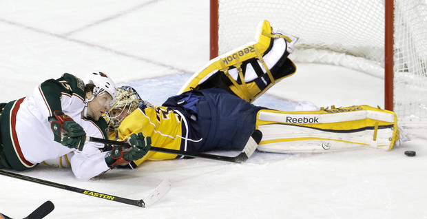 Nashville Predators goalie Pekka Rinne, right, of Finland, blocks a shot by Minnesota Wild right wing Dany Heatley (15) in the second period of an NHL hockey game on Saturday, March 9, 2013, in Nashville, Tenn. (AP Photo/Mark Humphrey)