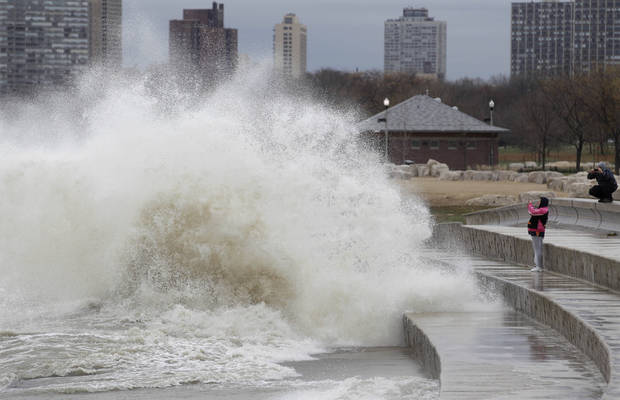 Onlookers take photos as strong waves created by superstorm Sandy crash against the Lake Michigan waterfront, Tuesday, Oct. 30, 2012, on the south side of Chicago. Strong winds from the outer edge of superstorm Sandy are ripping up near-record high waves on Lake Michigan. (AP Photo/M. Spencer Green) ORG XMIT: ILMG102