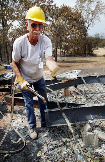 Retired oil-field welder Ron Elliott of Lexington finds a melted glass vase as he cuts apart the frame of a mobile home so it can be loaded on a truck as volunteers from the Southern Baptist Convention Disaster Relief team clean homeowners' property following last week's wildfires on Tuesday in Norman.  Photo by Steve Sisney, The Oklahoman <strong>STEVE SISNEY</strong>