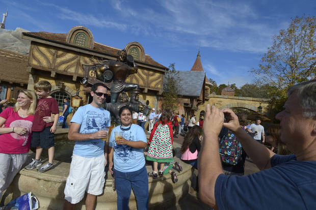Self-described Disney fanatics Derrick Weitlich, 31, third from left, and Leslie Martinez, 29, of Melbourne, Fla., pose for a souvenir photo in front of Gaston's Tavern during the grand opening of the New Fantasyland attraction at the Walt Disney World Resort's Magic Kingdom theme park in Lake Buena Vista, Fla., Thursday, Dec. 6, 2012. The new attraction is the largest expansion at the Magic Kingdom.(AP Photo/Phelan M. Ebenhack)