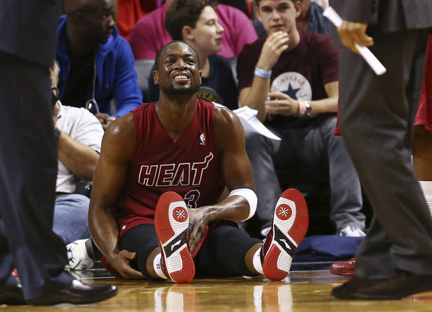 Miami Heat&#039;s Dwyane Wade (3) tends to his leg after being knocked to the floor during the second half of an NBA basketball game against the Oklahoma City Thunder in Miami, Tuesday, Dec. 25, 2012. The Heat won 103-97. (AP Photo/J Pat Carter)