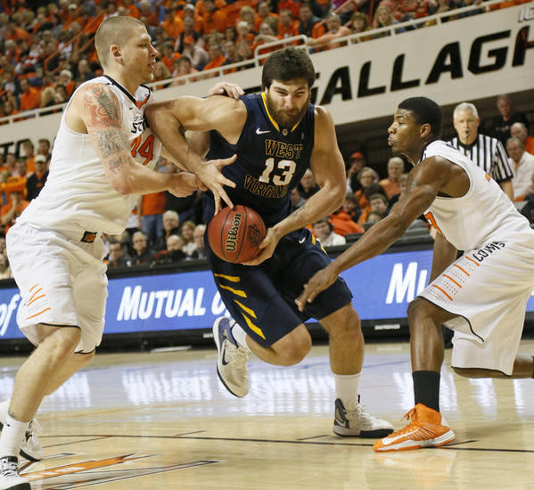 West Virginia's Deniz Kilicli (13) drives between Oklahoma State's Philip Jurick (44), left, and Marcus Smart (33) during an NCAA men's basketball game between Oklahoma State University (OSU) and West Virginia at Gallagher-Iba Arena in Stillwater, Okla., Saturday, Jan. 26, 2013. Photo by Nate Billings, The Oklahoman