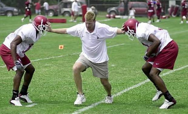 UNIVERSITY OF OKLAHOMA COLLEGE FOOTBALL, OU: Oklahoma defensive coordinator Mike Stoops, center, works on a drill with defensive backs Eric Bassey, left, and Tony Cade during practice Friday, Aug. 8, 2003, in Norman, Okla. (AP Photo/Norman Transcript, Kevin Ellis)