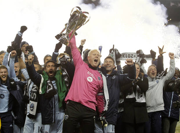 Sporting Kansas City goalkeeper Jimmy Nielsen, center, holds the MLS Cup as he and his teammates celebrate their 2-1 win over Real Salt Lake in the MLS Cup final soccer match in Kansas City, Kan., Saturday, Dec. 7, 2013. (AP Photo/Colin E. Braley)
