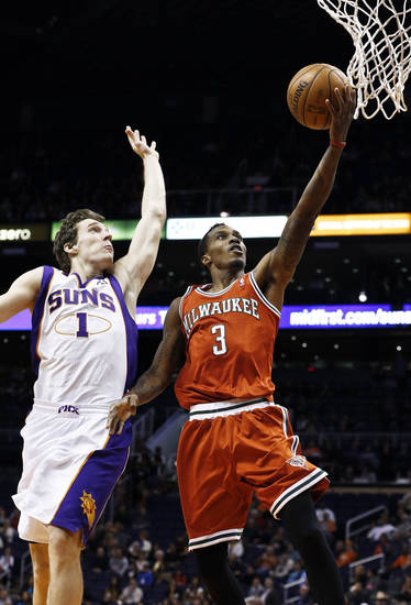 Milwaukee Bucks' Brandon Jennings (3) gets past Phoenix Suns' Goran Dragic (1), of Slovenia, for a fast-break score in the first half during an NBA basketball game on Thursday, Jan. 17, 2013, in Phoenix. (AP Photo/Ross D. Franklin)