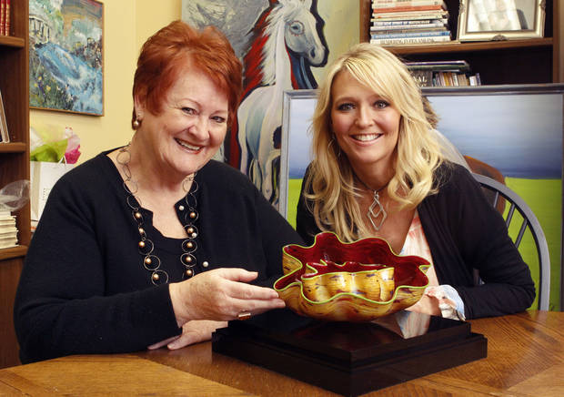 Edmond Fine Arts Institute Executive Director Mitzi Hancuff, left, and Assistant Executive Director Shannon Price look at a Moroccan Macchia Pair by Dale Chihuly, one of the auction items at Spring Sampler Evening of Art. PHOTOS BY PAUL HELLSTERN, THE OKLAHOMAN