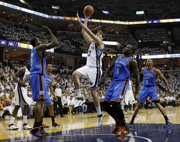 Memphis Grizzlies center Marc Gasol (33), of Spain, shoots against Oklahoma City Thunder forward Serge Ibaka (9) and Kendrick Perkins (5) during the first half of Game 3 of a second-round NBA basketball series on Saturday, May 7, 2011, in Memphis, Tenn. At right is Thunder guard Russell Westbrook (0). (AP Photo/Mark Humphrey) ORG XMIT: TNMH109
