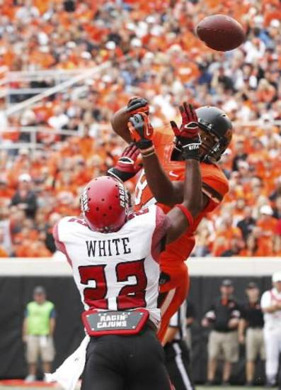Louisiana-Lafayette cornerback Melvin White (22) breaks up a pass intended for Oklahoma State wide receiver Tracy Moore (87) in the second quarter of an NCAA college football game in Stillwater, Okla., Saturday, Sept. 15, 2012. (AP Photo/Sue Ogrocki)