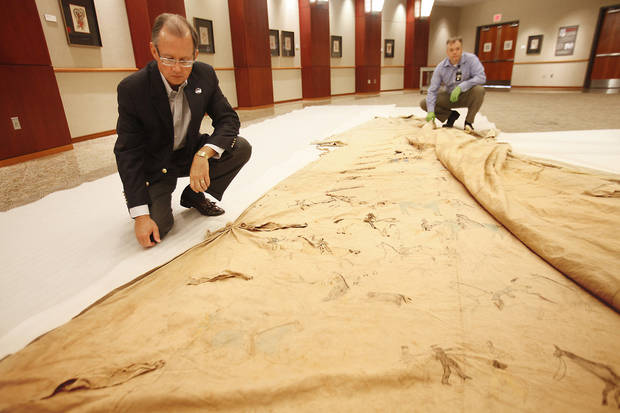 "Bob Blackburn, the executive director of the Oklahoma Historical Society, and Matt Reed, a curator at the Oklahoma Museum of History, look over a tepee used in the silent movie ""The Daughter of Dawn."" <strong>David McDaniel - The Oklahoman</strong>"