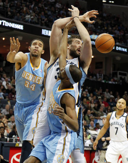 Denver Nuggets defenders JaVale McGee (34) and Corey Brewer (13) knock the ball away from Memphis Grizzlies center Marc Gasol, center, of Spain, in the first half of an NBA basketball game on Saturday, Dec. 29, 2012, in Memphis, Tenn. (AP Photo/Lance Murphey)