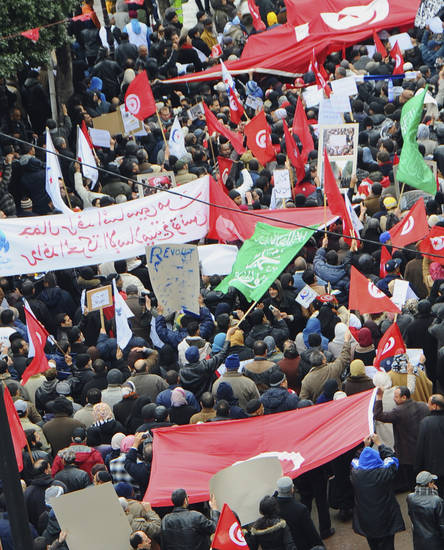 Protesters gather during a demonstration in Tunis Saturday  Feb 9, 2013. Several thousand supporters of Tunisia's ruling moderate Islamist party rallied in the capital in a pro-government demonstration Saturday, a day after the funeral of an assassinated opposition politician. The ruling Ennahda party had called for a show of support for the constitutional assembly, whose work on a new constitution suffered a severe setback after the killing of Chokri Belaid on Feb. 6, 2013 when leftist parties withdrew their participation. Protesters hurled insults at France, accusing the former colonial ruler of interfering in the North African country's politics. ( AP Photo/Hassene Dridi)