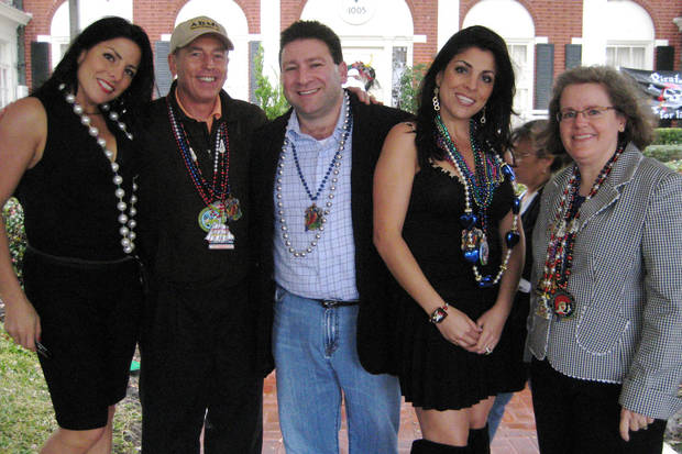 CORRECTS TO SAY KELLEY IS AN UNPAID SOCIAL LIASON TO MACDILL AFB, NOT STATE DEPARTMENT - In this Jan. 30, 2010 photo, Natalie Khawam, left, Gen. David Petraeus, Scott and Jill Kelley, and Holly Petraeus watch the Gasparilla parade from the comfort of a tent on the Kelley's front lawn in Tampa, Fla. Jill Kelley is identified as the woman who received threatening emails from Gen. David Petraeus' paramour, Paula Broadwell. Jill Kelley serves as an unpaid social liaison to MacDill Air Force Base in Tampa, where the military's Central Command and Special Operations Command are located. (AP Photo/The Tampa Bay Times, Amu Scherzer) TAMPA OUT; CITRUS COUNTY OUT; PORT CHARLOTTE OUT; BROOKSVILLE HERNANDO TODAY OUT; USA TODAY OUT; TV OUT; INTERNET OUT; MAGS OUT