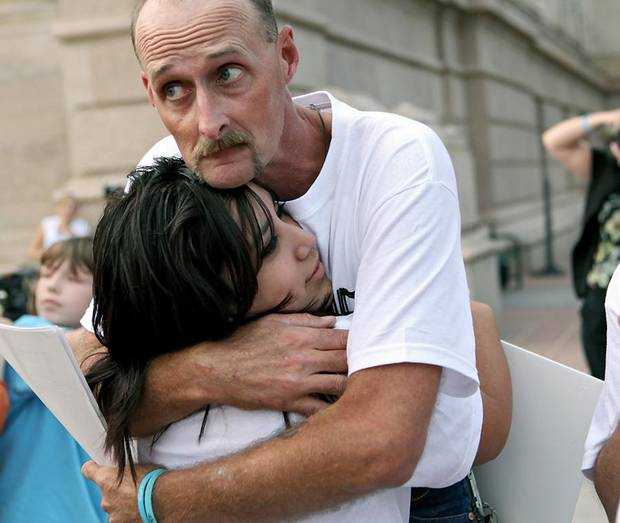 Kirk Smalley gets a hug from  Alexis Cedillo, a Putnam City West High School student during a Stand for the Silent event at the Oklahoma State Capitol in Oklahoma City on Tuesday, August 24, 2010. Kirk's son Ty Smalley committed suicide earlier this year after being bullied. Photo by John Clanton, The Oklahoman