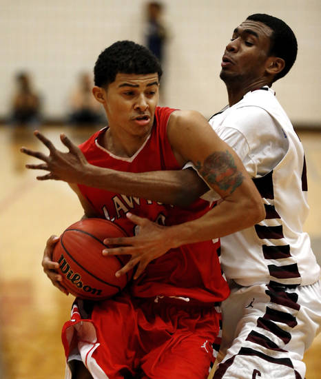 Lawton's Carl Tidmore is fouled by Capitol Hill's Aaron Brown in the consolation boys finals of the John Nobles Invitational Tournament on Saturday, Jan. 26, 2013  in Moore, Okla. Photo by Steve Sisney, The Oklahoman