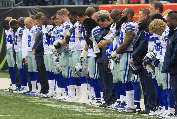 Dallas Cowboys players hang their heads during a moment of silence honoring teammate Jerry Brown who was killed in an automobile accident prior to an NFL football game against the Cincinnati Bengals, Sunday, Dec. 9, 2012, in Cincinnati. (AP Photo/Al Behrman)