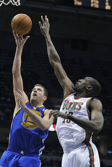 Golden State Warriors' David Lee, left, drives to the basket over Milwaukee Bucks' Ekpe Udoh during the first half of an NBA basketball game on Saturday, Jan. 26, 2013, in Milwaukee. (AP Photo/Jim Prisching)