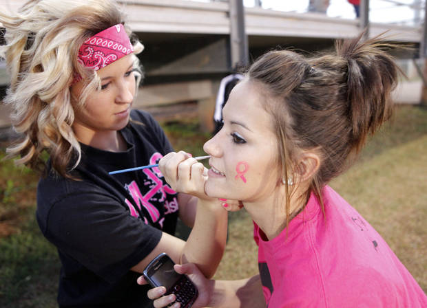 McCloud Cheerleader Lainie Barnes paints a pink ribbon on fellow cheerleader Sabrina Chute's face before the Douglass at McLoud football on Thursday, Oct. 18, 2012 in McLoud , Okla.  Photo by Steve Sisney, The Oklahoman