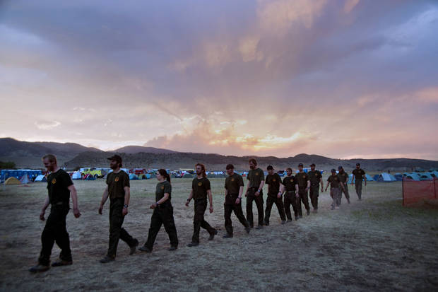 In this June 19, 2012, photo provided by the Colorado Army National Guard, firefighters from Coeur D'alene, Idaho march to dinner at sunset in the base camp for the High Park wildfire in Fort Collins, Colo. AP photo <strong>John Rohrer - AP</strong>