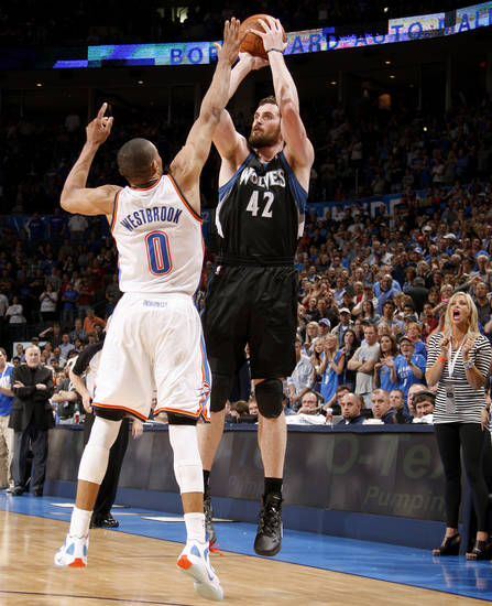 Minnesota's Kevin Love (42) shoots a three-point basket over Oklahoma City's Russell Westbrook (0) to send the game into overtime during an NBA basketball game between the Oklahoma City Thunder and the Minnesota Timberwolves at Chesapeake Energy Arena in Oklahoma City, Friday, March 23, 2012. Photo by Bryan Terry, The Oklahoman