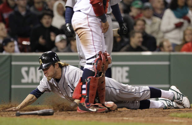 Oakland Athletics' Josh Reddick dives into home to score on a double by Seth Smith during the sixth inning against the Boston Red Sox in a baseball game at Fenway Park in Boston, Wednesday, May 2, 2012. (AP Photo/Elise Amendola)