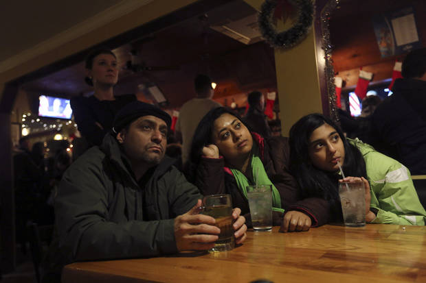Surendra Khera, left, Manjaree Daw, center and Indira Khera, of Simsbury, Conn., watch President Obama deliver his speech at the Iron Bridge restaurant, Sunday, Dec. 16, 2012 in Newtown, Conn. The president spoke during an interfaith vigil for the victims of the Sandy Hook Elementary School shooting. A gunman walked into the elementary school Friday and opened fire, killing 26 people, including 20 children. (AP Photo/Mary Altaffer)   ORG XMIT: CTMA122