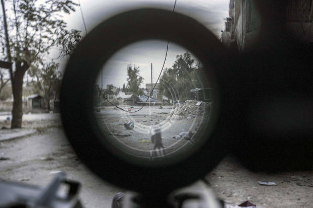 In this Friday, Nov. 02, 2012 photo, a sniper line-of-fire is seen through the scope of a rebel fighter's gun in the Karm al-Jebel neighborhood in Aleppo, Syria. U.N. officials and human rights groups believe President Bashar Assad's regime is responsible for the bulk of suspected war crimes in Syria's 19-month-old conflict, which began as a largely peaceful uprising but has transformed into a brutal civil war. However a video that appears to show a unit of Syrian rebels kicking terrified, captured soldiers and then executing them with machine guns raised concerns Friday about rebel brutality at a time when the United States is making its strongest push yet to forge an opposition movement it can work with. (AP Photo/Narciso Contreras)