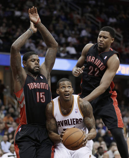 Toronto Raptors' Amir Johnson (15) and Rudy Gay (22) put pressure on Cleveland Cavaliers' Alonzo Gee during the second quarter of an NBA basketball game Wednesday, Feb. 27, 2013, in Cleveland. (AP Photo/Tony Dejak)