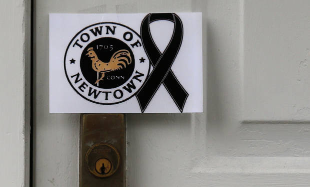 A sign showing the town seal and a black ribbon is posted on the door of an antique colonial home in the historic district near the funeral for six-year-old student shooting victim Jack Pinto in Newtown, Conn., Monday, Dec. 17, 2012. A gunman opened fire at Sandy Hook Elementary School in the town, killing 26 people, including 20 children before killing himself on Friday. (AP Photo/Charles Krupa) ORG XMIT: CTCK109