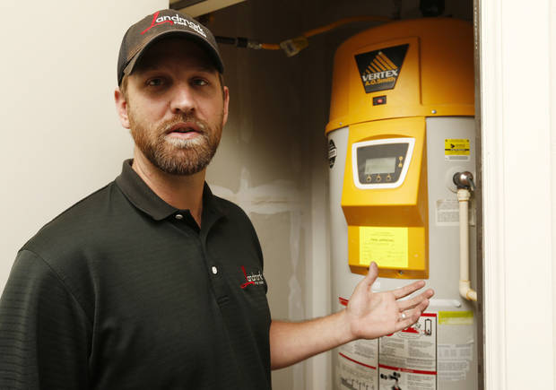 Houston Sneed director of construction, shows a gas water heater with hot water storage as well as on demand instant heating of water that is part of this Natural Gas Concept Home at 4500 Northfields on Friday, April 5, 2013 in Norman, Okla.  Photo by Steve Sisney, The Oklahoman