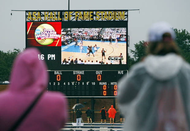 Softball fans watch Game 6 of the NBA Western Conference Finals between the Oklahoma City Thunder and the San Antonio Spurs on the scoreboard during a rain delay at  Game 3 of the Women's College World Series softball championship between OU and Alabama at ASA Hall of Fame Stadium in Oklahoma City, Wednesday, June 6, 2012.  Photo by Nate Billings, The Oklahoman