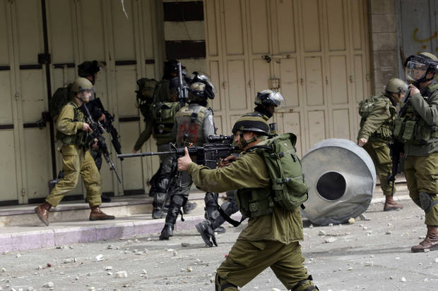 An Israeli soldier takes aim during clashes in the West Bank city of Hebron, following the death of Arafat Jaradat, a Palestinian prisoner held in an Israeli jail, Sunday, Feb. 24, 2013. The death of a 30-year-old Palestinian after interrogation by Israel's Shin Bet security service stokes new West Bank clashes, along with Israeli fears of a third Palestinian uprising. (AP Photo/Nasser Shiyoukhi)