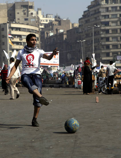 An Egyptian plays a game of street soccer before large crowds gather for a major rally called for by opposition groups in Tahrir Square, Cairo, Egypt, Friday, Nov. 30, 2012. Islamists approved a draft constitution for Egypt early Friday without the participation of liberal and Christian members, seeking to pre-empt a court ruling that could dissolve their panel with a rushed, marathon vote that further inflames the conflict between the opposition and President Mohammed Morsi. (AP Photo/Thomas Hartwell)
