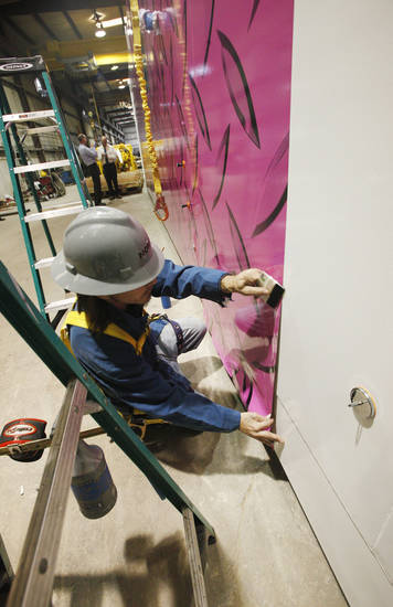 Jeremy Marney of Fastsigns of Oklahoma City applies a pink vinyl wrap to the driller's cabin of a Nomac Drilling rig on Thursday. The design was chosen to support breast cancer awareness. <strong>PAUL B. SOUTHERLAND - The Oklahoman</strong>