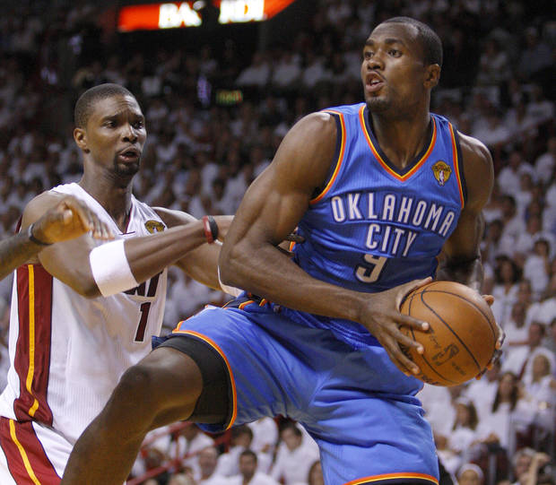 Oklahoma City's Serge Ibaka (9) grabs the ball beside Miami's Chris Bosh (1) during Game 4 of the NBA Finals between the Oklahoma City Thunder and the Miami Heat at American Airlines Arena, Tuesday, June 19, 2012. Photo by Bryan Terry, The Oklahoman
