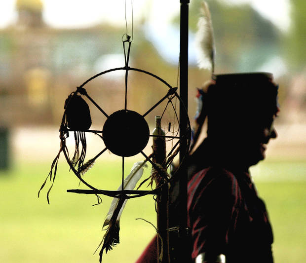 A dancer walks by an arts and crafts tent during the Tinker Intertribal Council Powwow. OKLAHOMAN ARCHIVE PHOTO BY BRYAN TERRY